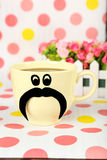 Yellow cup with paper mustache on colorful background Royalty Free Stock Image