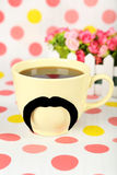 Yellow cup with paper mustache on colorful background Stock Photo