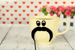 Yellow cup with paper mustache on white wooden background Royalty Free Stock Photography