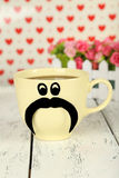 Yellow cup with paper mustache on white wooden background. Stock Images