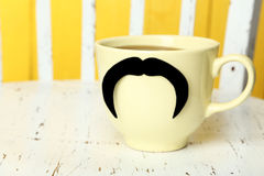 Yellow cup with paper mustache on white wooden background Royalty Free Stock Images