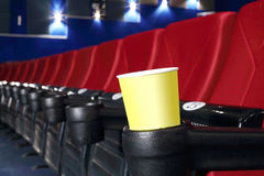 Yellow cup for popcorn is stand at red seat Royalty Free Stock Photos