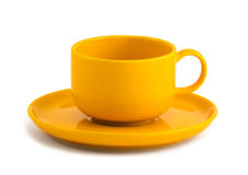 Yellow cup and saucer Stock Photos