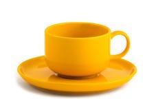 Yellow cup and saucer Stock Photos