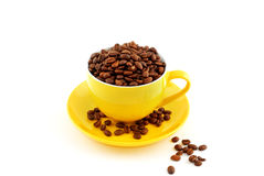 Yellow cup with saucer full of coffee beans Royalty Free Stock Images