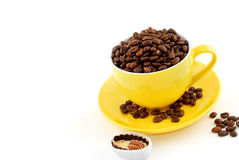 Yellow cup with saucer full of coffee beans Royalty Free Stock Photo