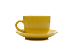 A yellow cup and saucer on white Royalty Free Stock Photography