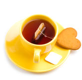 Yellow cup with tea bag and heart-shaped cookie Royalty Free Stock Image