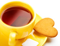 Yellow cup with tea bag and heart-shaped cookie Stock Photography