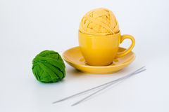 Yellow cup, two balls of yarn and knitting needles Royalty Free Stock Images