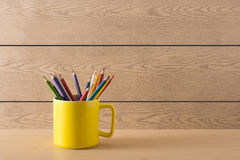 Yellow cup on the wood texture Stock Images