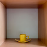 Yellow cup on a wooden square shelf. Stock Photo