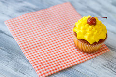 Yellow cupcake on a napkin. Royalty Free Stock Images