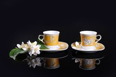 Yellow cups and flowers. Yellow cups on black with jasmine flower Stock Photo