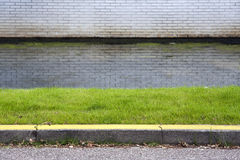 Yellow curb. Grass, water and a yellow curb. No way to park here Stock Photos