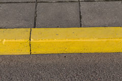 Yellow curb stone border Royalty Free Stock Images