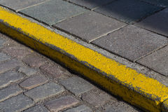 Yellow curb stone border. In an old town road Royalty Free Stock Photography