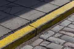Yellow curb stone border. In an old town road Stock Photo