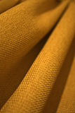 Yellow curtain. A background of a close up of a textured yellow curtain Royalty Free Stock Photo