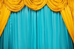 Yellow curtains of a classical theater scene. Theater stage with yellow and blue curtains Royalty Free Stock Photos