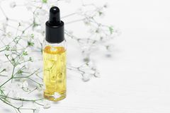 Cuticle oil. Yellow cuticle oil bottle on a white wooden table background. Fingernail care concept stock image