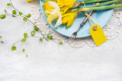 Yellow daffodils on blue plate with fork and table sign, spring decoration. Top view, frame Royalty Free Stock Photo