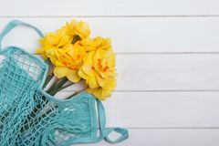 Yellow daffodils in the net bag on the white wooden table. With copy space royalty free stock photo