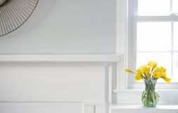 Yellow Daffodils in vase on white mantle Royalty Free Stock Image