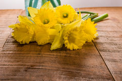 Yellow dafodills on wooden table Royalty Free Stock Photo
