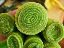 Leek cut section for cooking. Yellow daisy moonflower marguerite flower with green grass around. Summer Stock Images