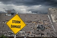 Free Yellow Damage Warning Sign In Front Of Storm Damaged Roof Of House Stock Photo - 129916460