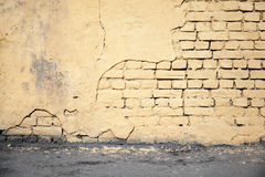 Yellow damaged brick wall and asphalt Royalty Free Stock Photos