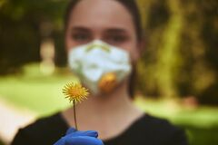 Yellow dandelion on the foreground in hands of blurred girl in protective mask and gloves on the background, quarantine