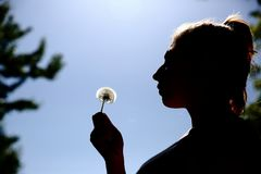 The teenager gently blows and spreads the dandelion seeds against the blue sky. stock photos