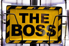 Yellow danger colored sign saying `The Boss` Stock Photography