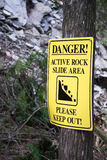 Yellow Danger Please Keep Out Rock Slide. Yellow danger sign. Yellow sign with danger active rock slide area please keep out. Rock slide in conservation park Royalty Free Stock Image