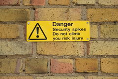 Yellow danger sign on a brick wall Royalty Free Stock Photos
