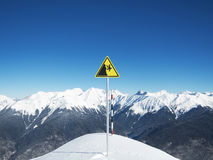 Yellow danger sign on ski slopes on the background of sky and winter mountains Stock Images