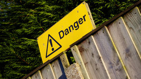 Yellow Danger sign on wooden fence Royalty Free Stock Photo
