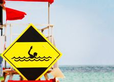 Yellow danger signal depicting a drowning swimmer. In the waves of a rough sea Royalty Free Stock Photography