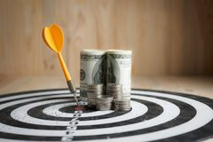 Yellow dart arrow hit the center target of dartboard and money c. Oin metaphor marketing or saving money concept, on wood background Stock Image