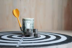 Yellow dart arrow hit the center target of dartboard and money c. Oin metaphor marketing or saving money concept, on wood background Royalty Free Stock Images