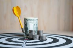 Yellow dart arrow hit the center target of dartboard and money c. Oin metaphor marketing or saving money concept, on wood background Stock Images