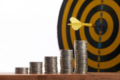 Yellow dart hit in the center of a target with stack of coins. On white background with copy space. A idea about money / currency investment that must decide or Royalty Free Stock Photo