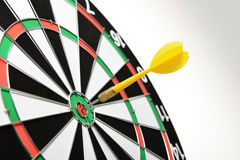 Yellow dart hitting target center. Ywllow dart hitting target center on white background Stock Image
