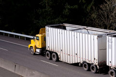 Yellow day cab big rig semi-truck on the road Royalty Free Stock Photos