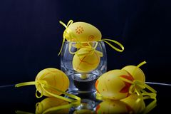 Easter eggs on a mirror. Yellow decorative easter eggs in glass and on a mirror with violet background royalty free stock images