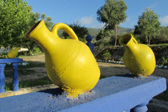 Yellow decorative pot. S standing on blue wall outside. decorative clay pot with handle, green trees behind royalty free stock images