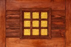 Yellow decorative stained-glass window. In the reddish lacquered wooden frame stock image