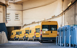 Yellow delivery vans trucks distribution. Row of yellow delivery and service van, trucks and cars in front of the entrance of a warehouse distribution logistic Royalty Free Stock Images